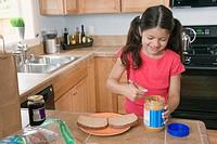 Hispanic girl making peanut butter and jelly sandwich