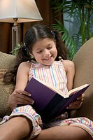 Hispanic girl reading on sofa