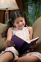 Hispanic girl reading on sofa