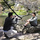 Man taking photograph on Asian woman in park