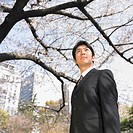 Low angle view of Asian businessman in urban park