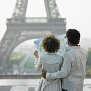 Couple looking at map next to Eiffel Tower
