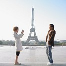 Couple taking photograph in front of Eiffel Tower