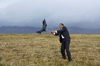 Businessman in windy rural area with broken umbrella
