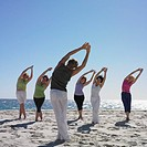 Group of women stretching with instructor on beach