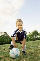 Young girl in athletic gear with soccer ball