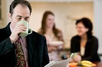 Businessman drinking coffee with family in background