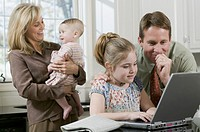 Father helping daughter use laptop while mother holds baby