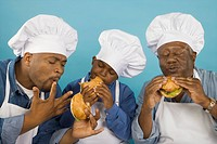 Multi-generational African male family members in chefÆs hats eating hamburgers