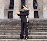 Businessman looking at cell phone on stone stairs