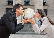 Businesspeople kissing globe in front of building