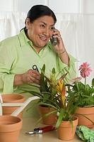 Senior Hispanic woman gardening indoors and using telephone