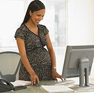 Pregnant African businesswoman at desk