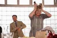 Mature couple in kitchen, woman tearing hair