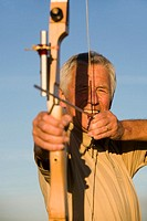 Senior adult woman using bow and arrow, close-up