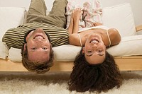 Young couple lying headfirst on sofa