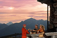 Couple taking break at alpine hut, peasant woman serving them