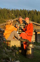 Couple sitting in front of alpine hut, toasting peasant woman