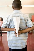 Boy holding paper airplane behind back in classroom