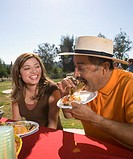 Hispanic father and adult daughter eating at picnic table