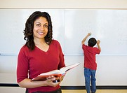 Female teacher with student writing on whiteboard in background
