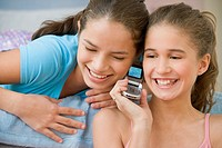 Hispanic sisters using same cell phone