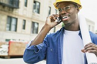 African man wearing hard hat using cell phone