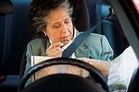 Senior Hispanic woman looking at map in car