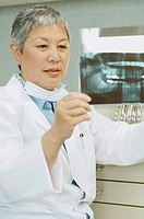 Senior Asian female dentist looking at x-rays (thumbnail)