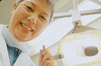 Senior Asian female dentist adjusting light