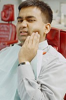 Indian man in dentist's chair with jaw pain