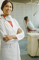 Indian female dentist smiling with patient in background