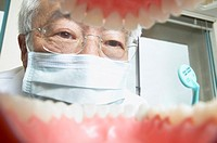 Shot from mouth looking out at senior Asian male dentist