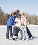 Family in ice skates hugging