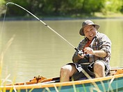 Man in small boat reeling in fish