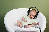 Baby in chair wearing adult headphones