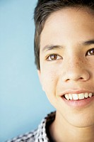 Close up studio shot of Asian boy smiling