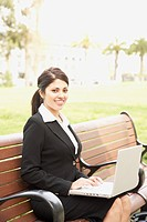 Hispanic businesswoman using laptop on bench outdoors