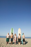 Multi-ethnic surfers in front of surfboards at beach
