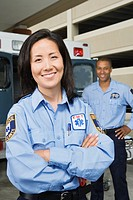 Asian female paramedic with co-worker in background