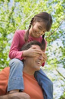 Hispanic father with daughter on shoulders