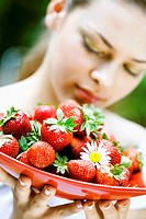 Young woman holding a dish of strawberries
