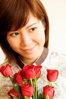 Close-up of a young woman smiling and holding a bouquet of red roses