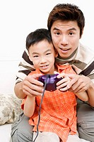 Portrait of a boy and his father playing a video game