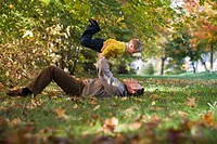 Father lying in meadow, lifting son 6-9