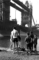 Boys by the River Thames at Tower Bridge, London, c 1910s Boys standing on the bank of the River Thames beside Tower Bridge  One is drying himself aft...