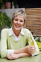 Portrait of a mature woman holding a bottle of wine and smiling