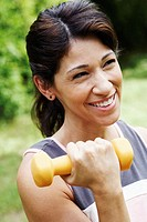 Close-up of a mature woman exercising with a dumbbell and smiling