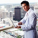 Portrait of a businessman using a laptop in a balcony