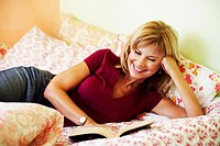 Close-up of a mature woman lying on the bed reading a book